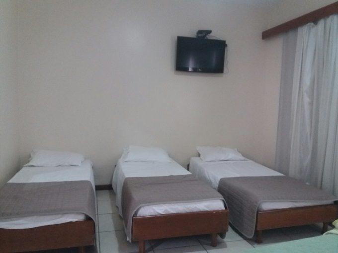 Três camas lado a lado em um dos quartos do Champagnat Praia Hotel Vila Velha