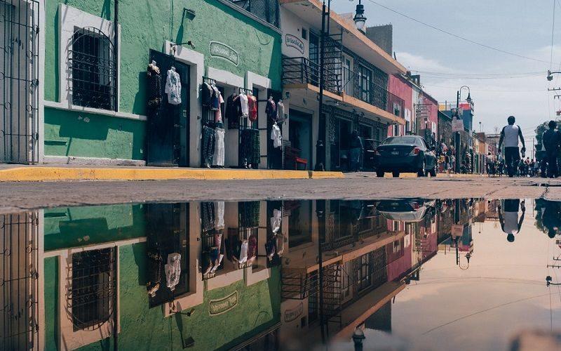 Rua em que é possível ver o funcionamento do transporte em Puebla, com alguns carros passando.