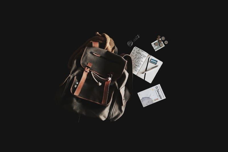 """Mochila, documentos, um caderno de anotações e um livro """"O Pequeno Príncipe"""""""