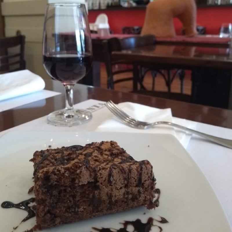 Bolo de chocolate em primeiro plano e taça de vinho ao fundo
