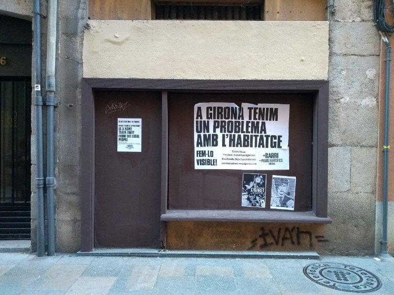 """Cartaz colado em uma parede com os dizeres """"Em Girona temos um problema de habitação. Façamos isso visível"""", escritos em catalão"""