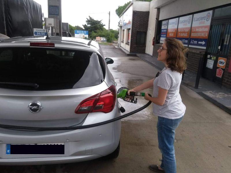 Mulher jovem abastecendo um carro na França