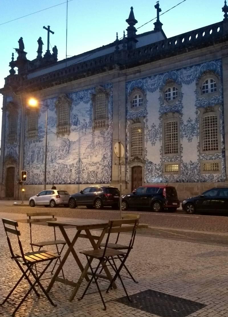 Mesinhas de bar no Porto, em frente à famosa Igreja do Carmo, cuja fachada é coberta de azulejos azuis