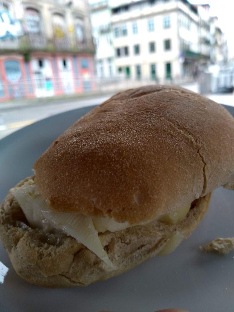 Sanduíche de queijo da Serra da Estrela em primeiro plano, com prédios do Porto ao fundo