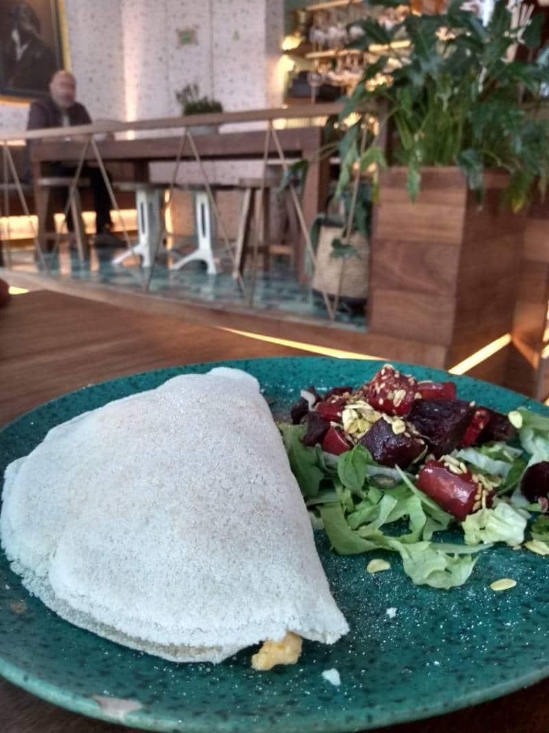Tapioca servida ao lado de uma salada de folhas e beterraba no Nicolau
