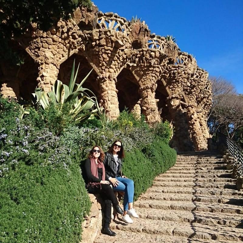 Duas mulheres de cerca de 30 anos sentadas em uma mureta em frente a construções de pedra no Parque Güell
