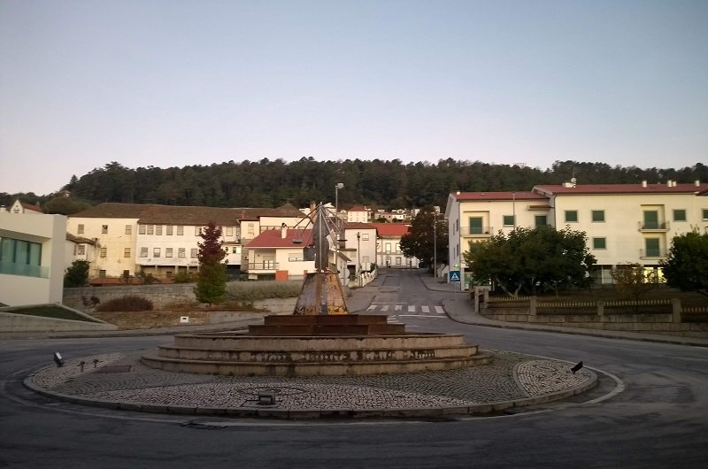 Rótula em cidade histórica de Portugal. Atrás dela podem ser vistas casinhas brancas com telhas cor de barro.