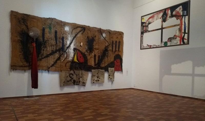 Duas obras na Fundação Joan Miró, em Barcelona. A primeira delas trata-se de uma tapeçaria com partes expostas. A segunda é um quadro parcialmente queimado pendurado no meio do museu para que seja possível observar sua sombra.