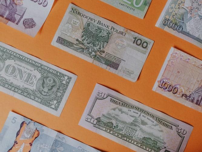 Remessa Online ou TransferWise: foto de notas de diferentes divisas sobre um fundo laranja