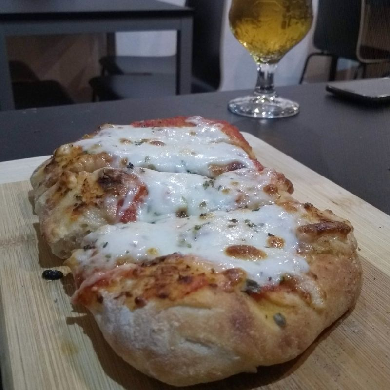 Focaccia de queijo em primeiro plano. Ao fundo é possível ver metade de um copo de cerveja.