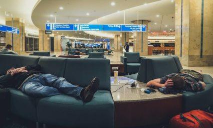 Duas pessoas a dormir no aeroporto.
